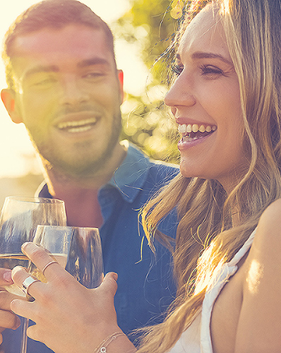 Couple on a date at as restaurant. There is food and wine on the table. They are happy and laughing. Outdoors at sunset.